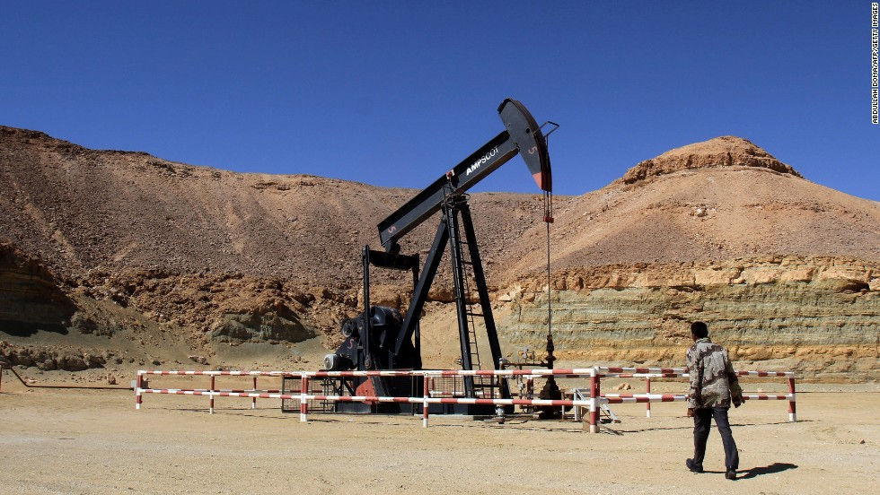 A security worker walks by an oil drill on March 23 at the al-Ghani oil field, owned by the Harouge Oil Operations company, near the city of Waddan.