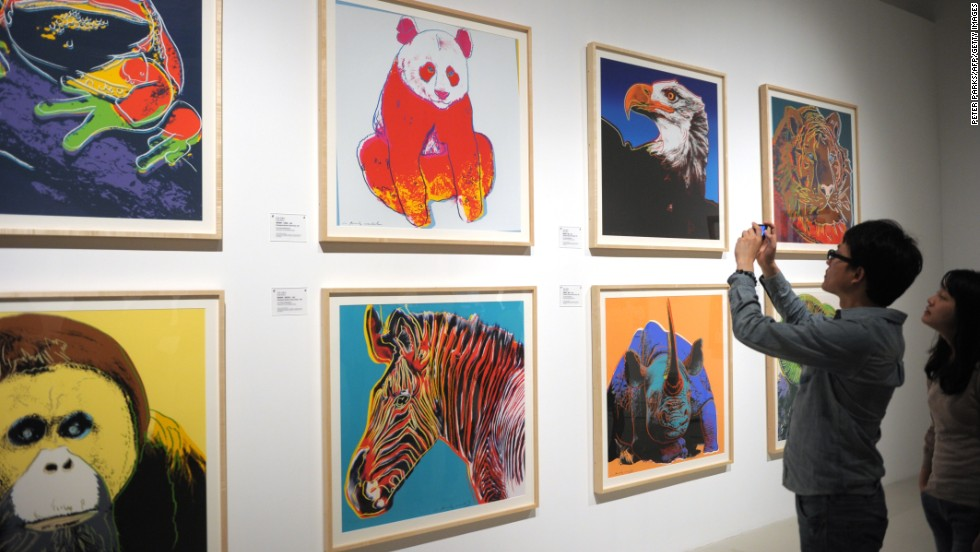 """A visitor takes photos at the exhibition """"Andy Warhol: 15 Minutes Eternal"""" showing at Shanghai's Power Station of Art from April 28- May 31.  The show excluded his iconic portraits of Chairman Mao."""