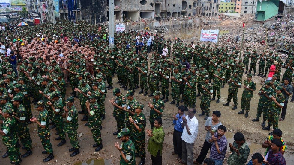 """Members of the Bangladesh army pray at the site of the collapsed Rana Plaza in Savar near Dhaka on Tuesday, May 14. The army-led effort to search for bodies has ended nearly three weeks after the nine-story building collapsed. <a href=""""http://www.cnn.com/2013/05/14/world/asia/bangladesh-building-collapse-aftermath/?hpt=hp_t2"""">The final death toll stands at 1,127</a>."""