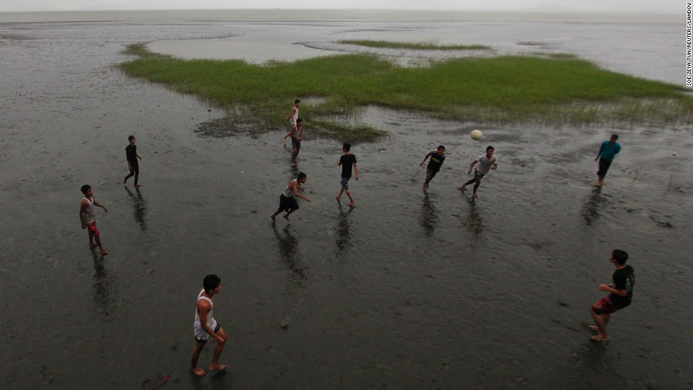 Young men play soccer on the beach in Sittwe on May 14.