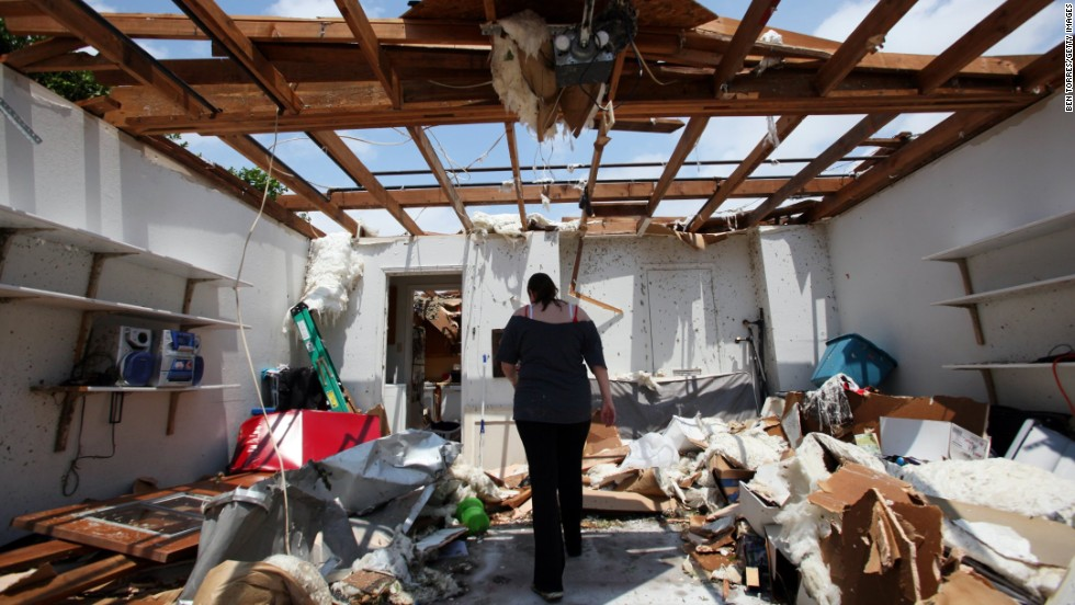 Beth Poledna walks through her garage on May 16 in Cleburne, Texas, as she begins the cleanup after a tornado swept through the area.