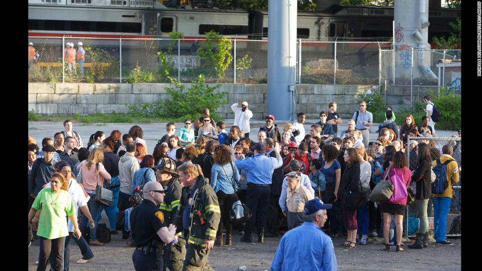 Passengers gather as they wait for a bus to pick them up from the scene of the collision.