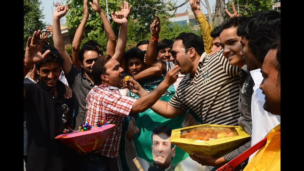 Supporters of Nawaz Sharif dance and eat sweets as they celebrate the party's win in Lahore on Wednesday, May 15.