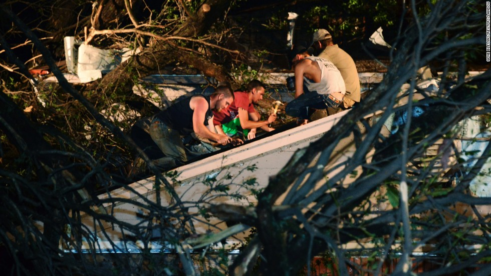 Residents repair the roof of a neighbor's damaged house after a tree fell on it in Shawnee on May 19.