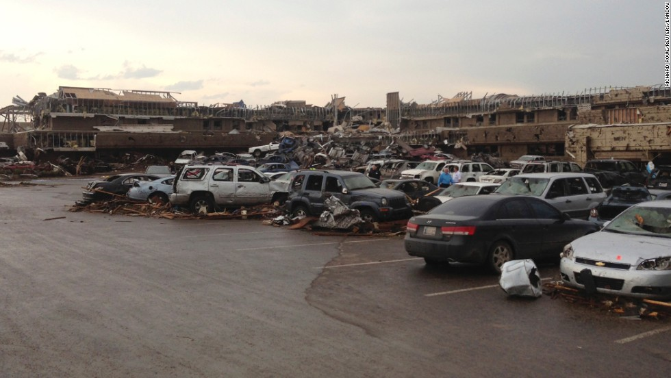 A shopping center parking lot is covered with debris and damaged cars on May 20.