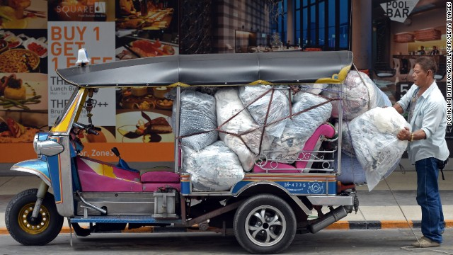 A Thai worker loads packs of clothes on a Thai tuk-tuk at shopping mall in Bangkok on May 20.