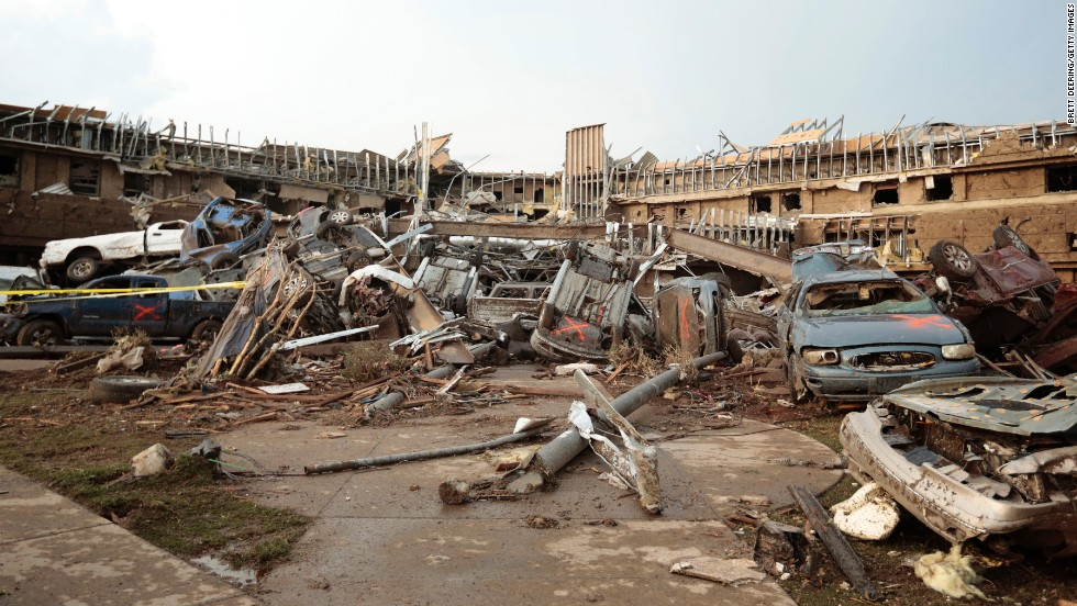 Cars marked with an orange X, meaning they have been checked for occupants, are piled up in front of the entrance to the damaged Moore Medical Center on May 20.