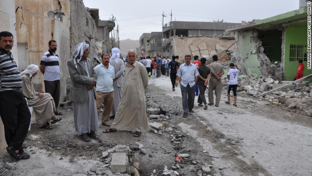 Iraqis inspect damages at the site of two car bomb blasts in Tuz Khurmatu in the Salaheddine province, on May 21, 2013.