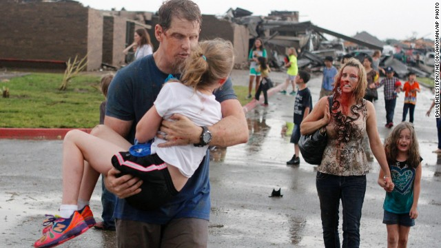 Steve and LaDonna Cobb take children away from Briarwood Elementary after a tornado destroyed the school Monday.