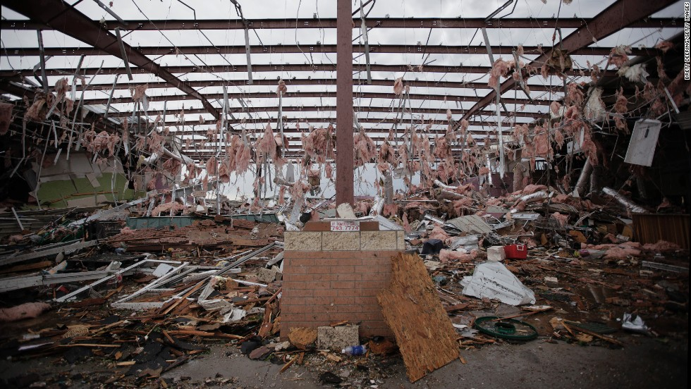 Tufts of pink insulation hang from the rafters of a store in Moore on May 21 that was destroyed in the storm.