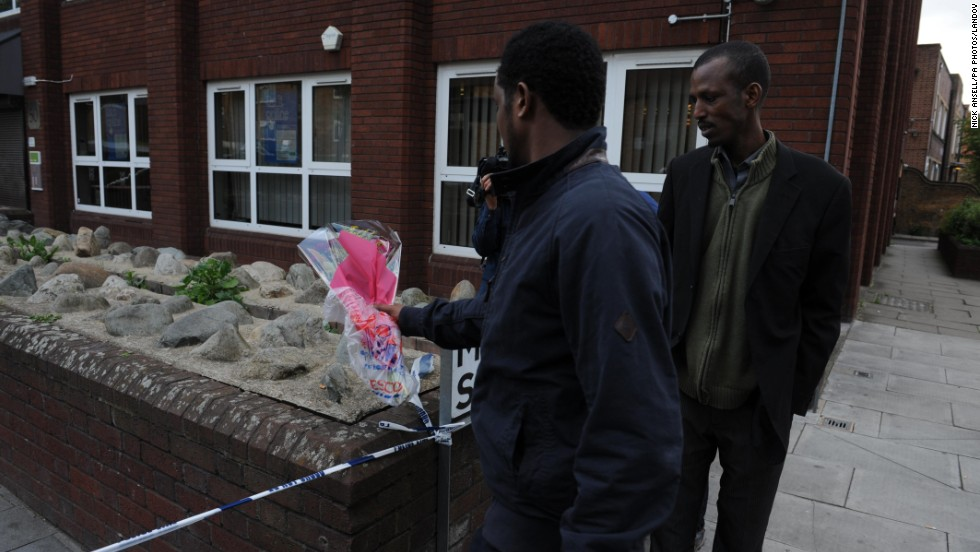 Men place flowers near the scene on John Wilson Street.
