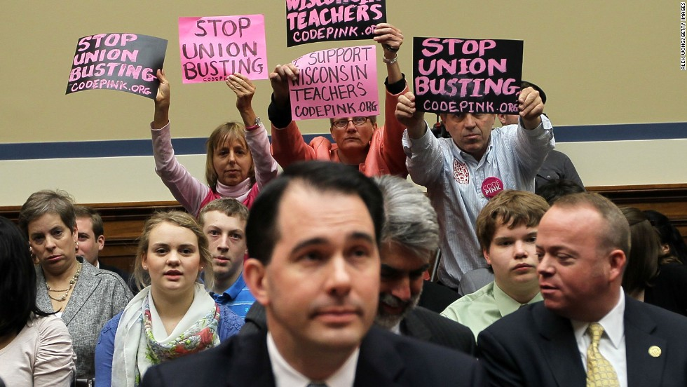 Left to right: Benjamin, Liz Hourican and Tighe Barry hold signs to protest as Wisconsin Gov. Scott Walker, center, takes his seat during a hearing before the House Oversight and Government Reform Committee on April 14, 2011, in Washington.