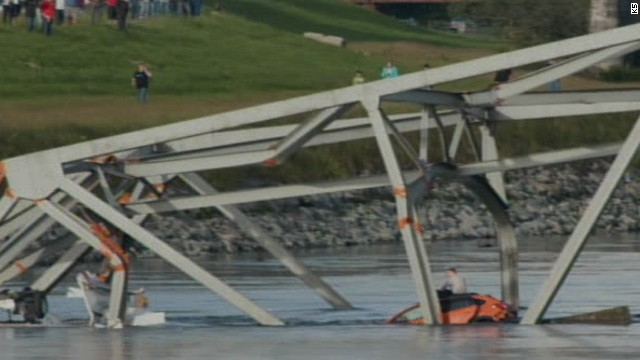 A person sits on top of a car in the Skagit River after the bridge collapsed.