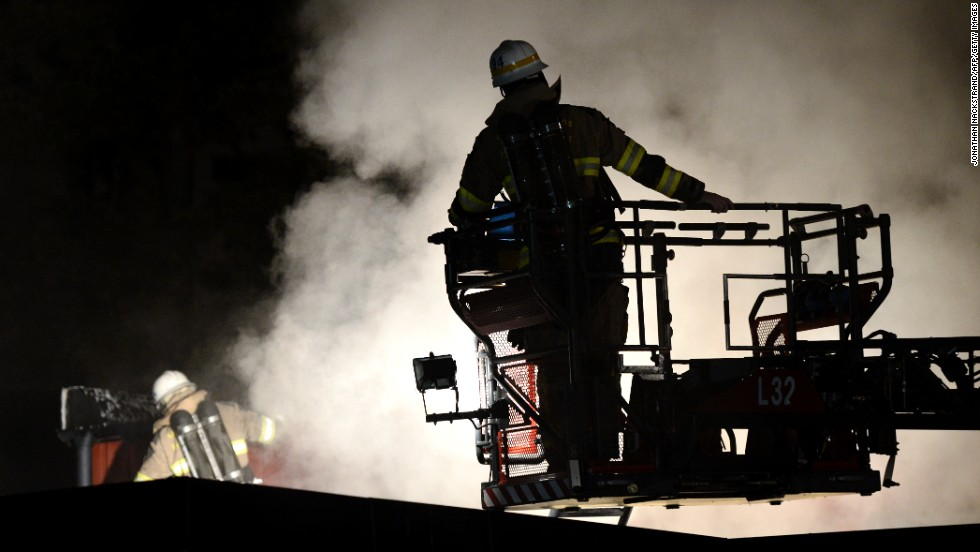 Firemen extinguish a blaze at a nursery school in the Stockholm suburb of Kista after riots in Sweden early Friday, May 24. Early media reports said the riots, which started Sunday, might have been triggered by police killing a 69-year-old man wielding a machete. But police say they are unsure of the cause.