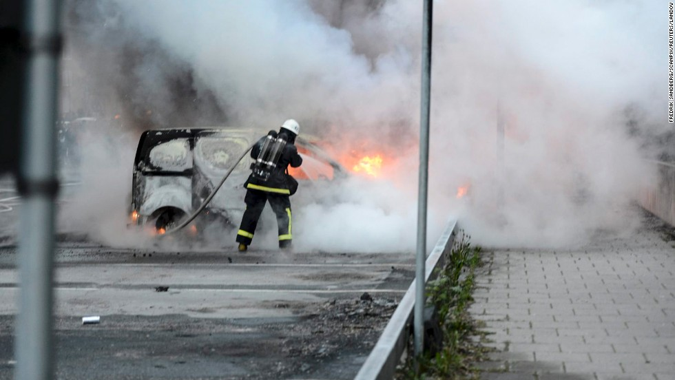 Firemen extinguish a burning car in Rinkeby outside of Stockholm on May 23.