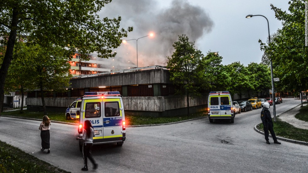 Police officers secure an apartment building after overnight riots in Husby on Monday, May 20. The building had to be evacuated after a fire spread inside the parking garage.