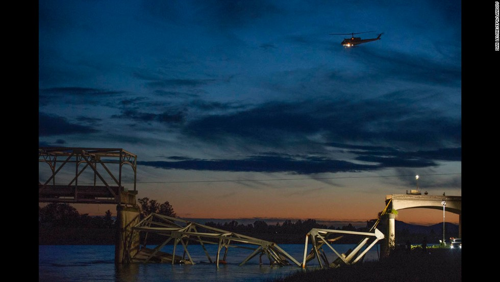 A helicopter leaves the scene as night falls after the collapse on May 23.