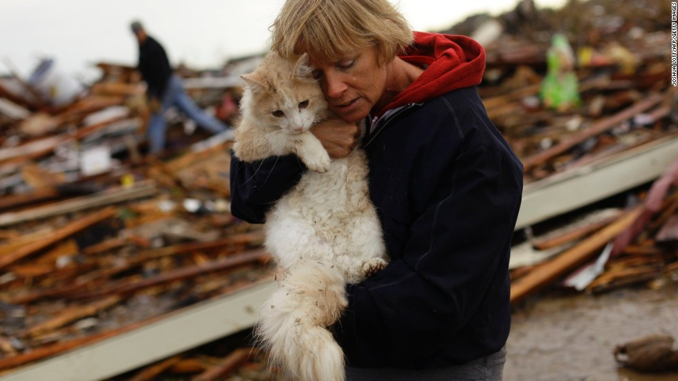 June Simson embraces her cat Sammi after she found him standing on the rubble of her destroyed home on May 21.