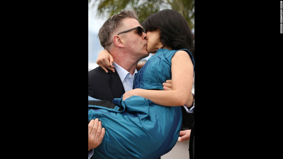 """Alec Baldwin and wife Hilaria Thomas kiss at Cannes' """"Seduced and Abandoned"""" photocall on May 21."""