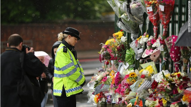 A police officer looks at flowers on Friday laid where Lee Rigby of the 2nd Battalion the Royal Regiment of Fusiliers was killed.