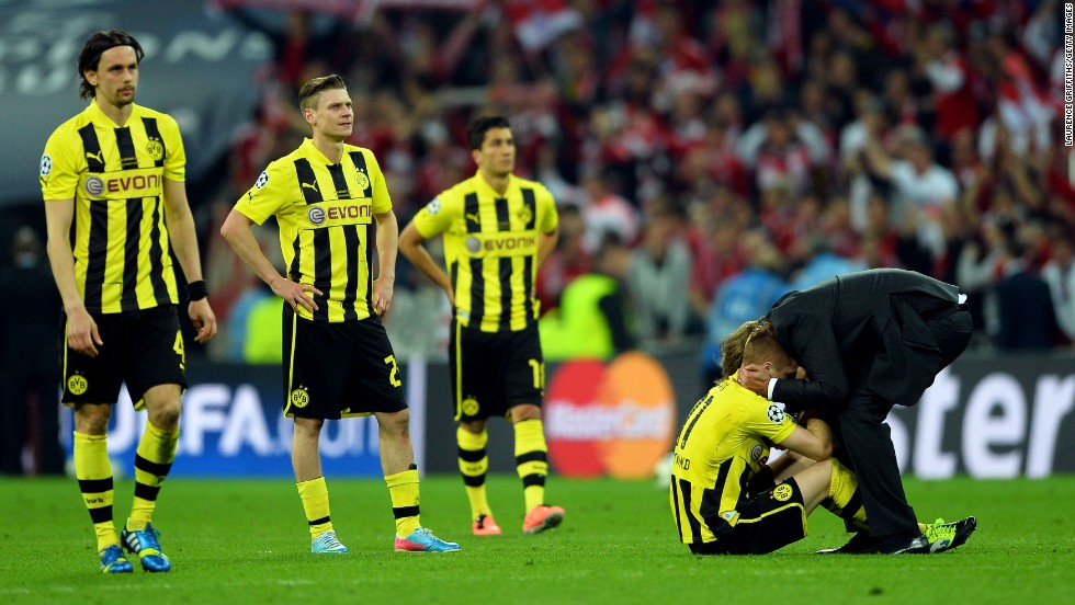 Head Coach Jurgen Klopp, right, of Borussia Dortmund consoles his players after losing to Bayern Munich in the championship match.