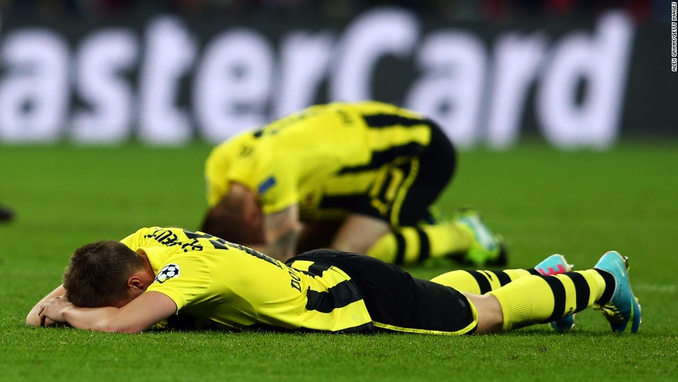 Dortmund players lie on the field in defeat after losing to Bayern 2-1.