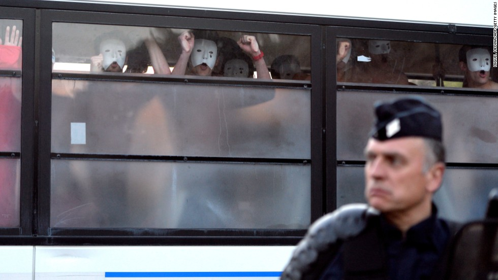 Bare-chested men wearing white masks, members of anti-gay group Hommen, shout slogans as they are detained in a police bus during a demonstration against a bill legalizing same-sex marriages on May 17 in Paris.