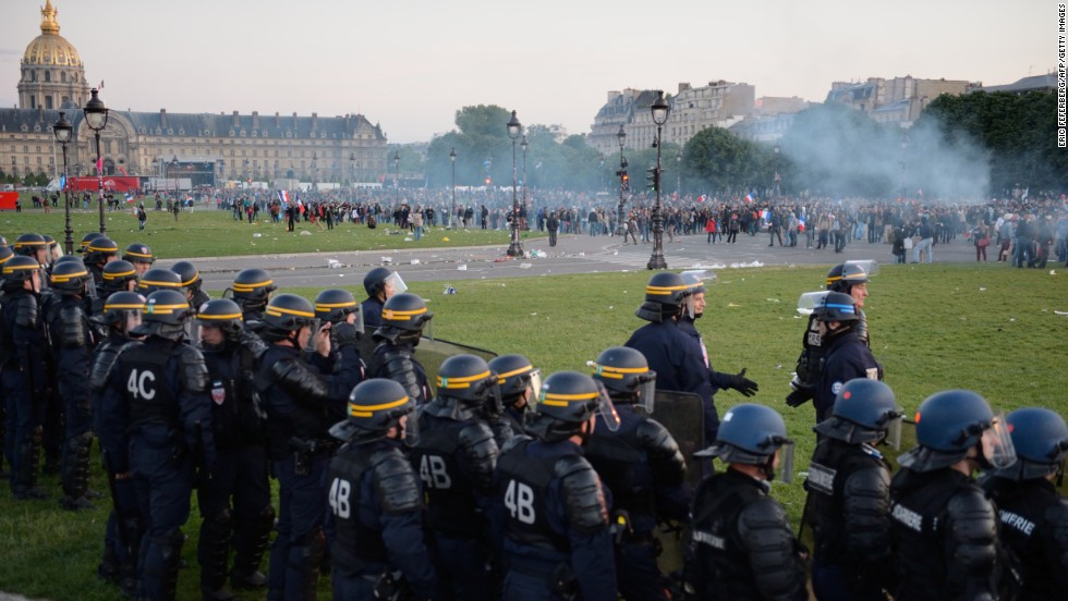 Riot police stand in a line facing protesters on May 26.