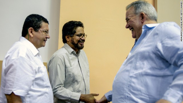 FARC-EP head Ivan Marquez (C) shakes hands with Venezuelan OAS ambassador Roy Chaderton (R) in Havana on Sunday.