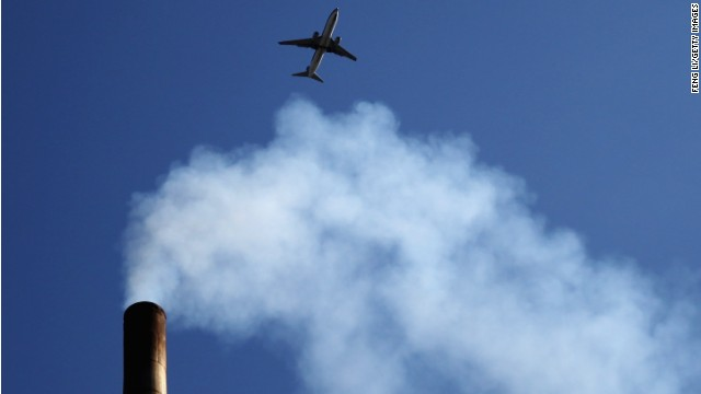 A plane flies over a Beijing chimney in May 2012. China's energy needs are now the highest in the world.