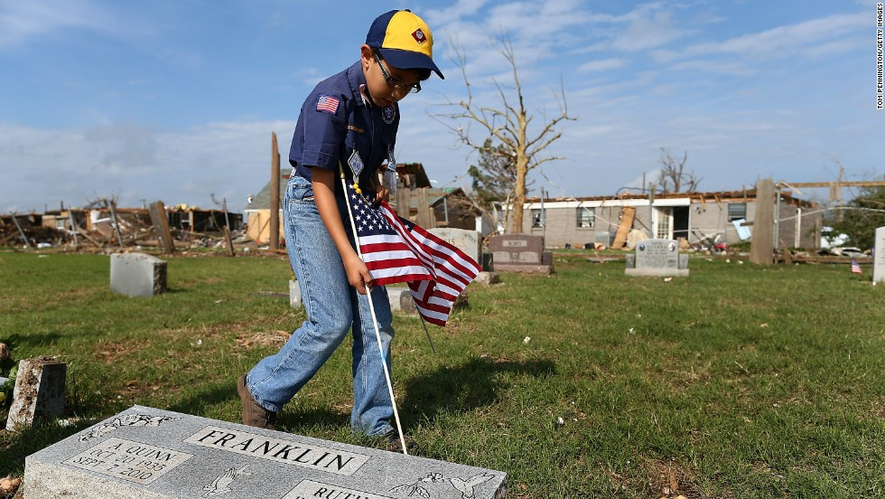 Boy Scout Patrick Mach places an American flag on a veteran's grave in Moore, Oklahoma, on Saturday, May 25. The annual project took place in Moore Cemetery, which is next to a neighborhood that the May 20 tornado heavily damaged.