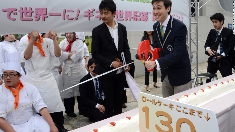 An officer from Guinness World Records (second right) measures a 130.68m long cake in Tokyo on April 17, 2013. Around 90 patissiers and students used 54kg flour, 43kg sugar and 2,682 eggs, beating the previous record of 115.09m for the longest cake in the world.