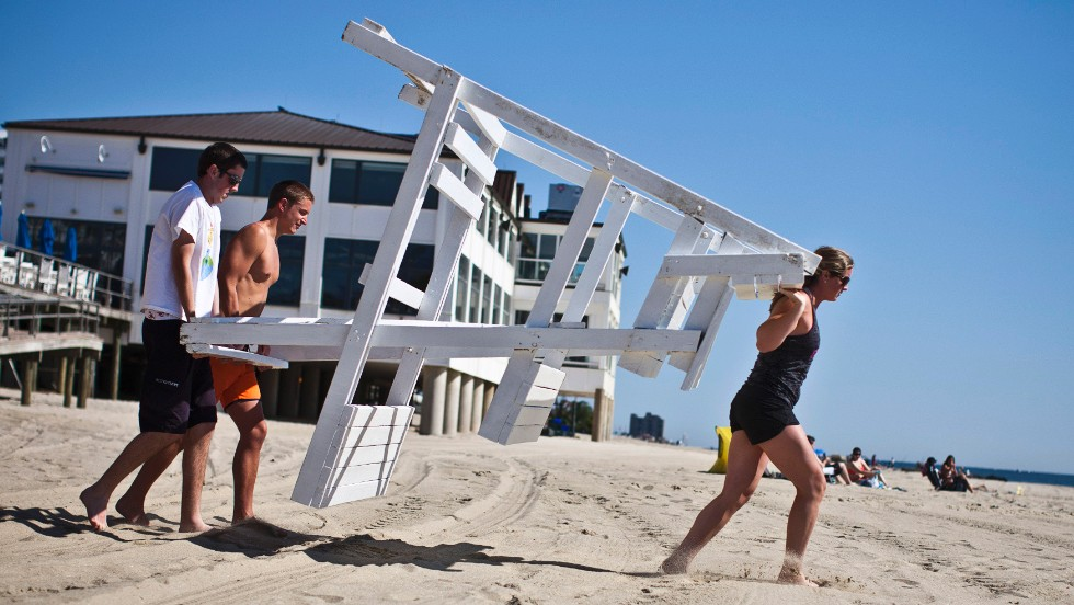 Lifeguards carry a chair into place on Monday, May 27, in Long Branch, on the first weekend of Jersey Shore beaches re-opening to the public since Superstorm Sandy devastated parts of the coastline seven months ago.