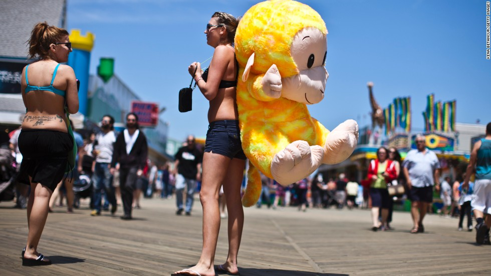 Nicole Zupp carries a stuffed monkey on the Seaside Heights boardwalk, where vendors are once again open for business.