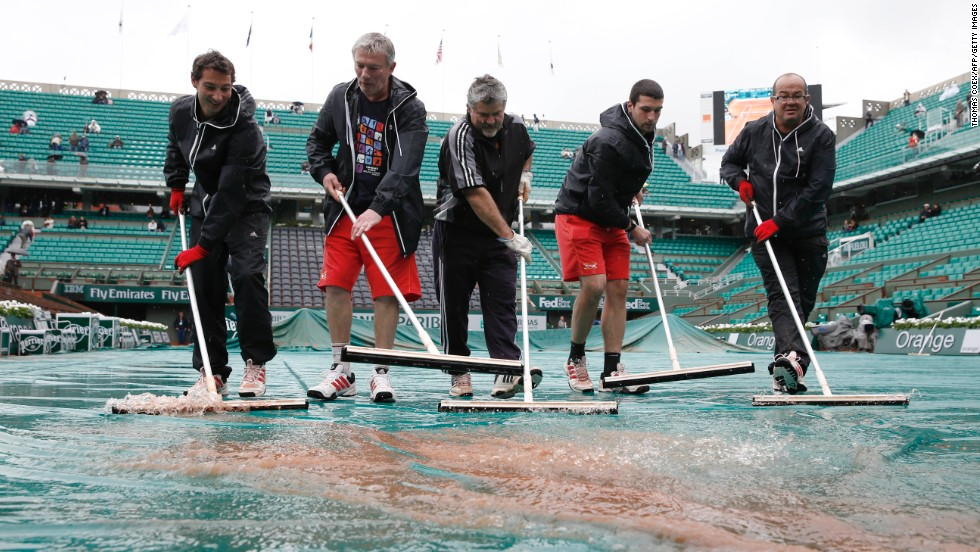 Employees remove water from a tarpaulin covering the Philippe Chatrier central court on May 28.