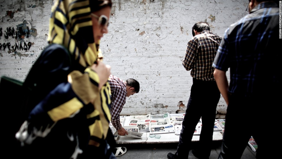 Iranians read the headlines on the front pages of newspapers unveiling the approved presidential candidates on May 22 in Tehran.