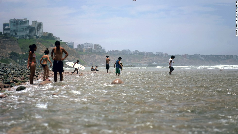 People wade in the water at a beach in Lima.