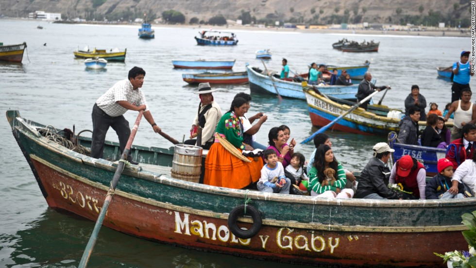 People accompany a maritime procession at the fishing port of Chorrillos in Lima.