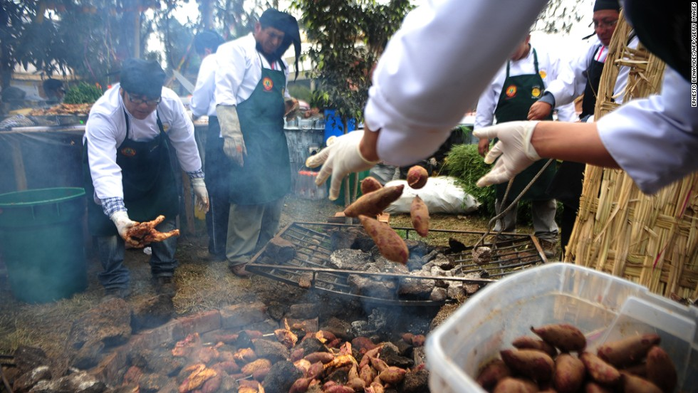 People throw potatoes into a pachamanca, a traditional Peruvian dish cooked on hot stones.