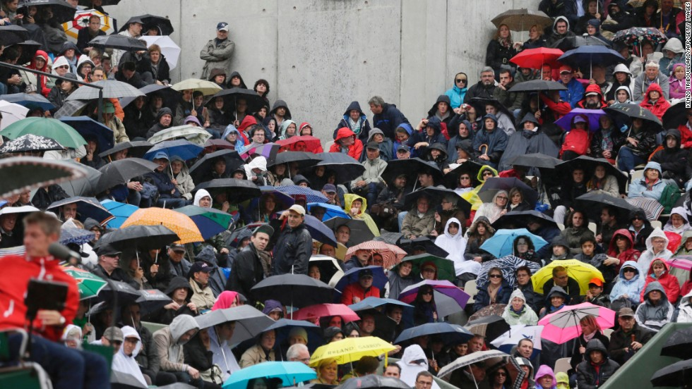 Spectators sit in the rain at the Suzanne Lenglen court on May 30.
