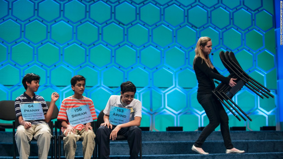 The final three competitors, Pranav Sivakuma, left, Sriram J. Hathwar, center, and Arvind V. Mahankali chat as former competitors' chairs are removed from the stage.
