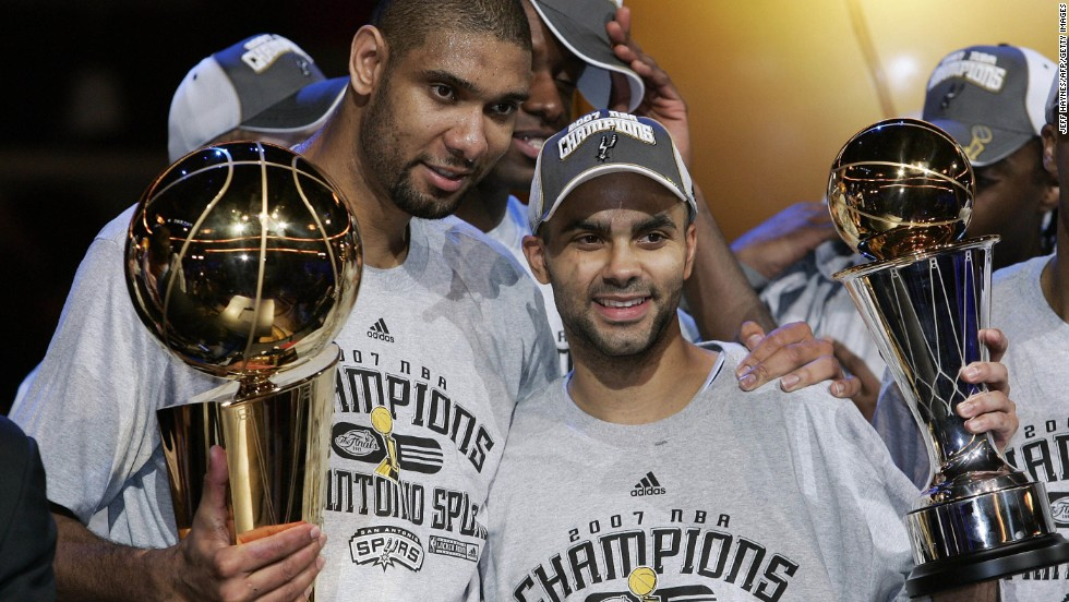 Duncan poses with the NBA Championship Larry O'Brien Trophy while teammate Tony Parker hoists the MVP Trophy after leading the Spurs to their fourth NBA title with their 2007 sweep of the Cleveland Cavaliers.