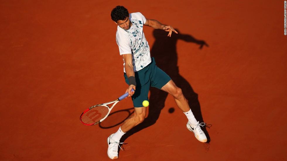 Dimitrov plays a forehand to Djokovic.