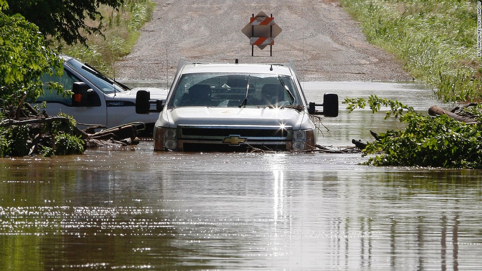 Two pickup trucks are pictured stuck in high water along North West 23rd Street in El Reno on June 1. Heavy rain has caused flooding in the area.