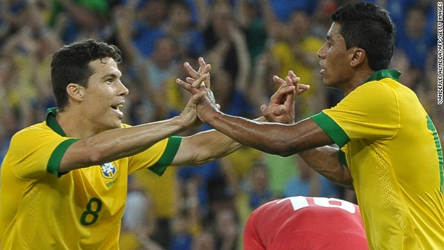 Brazil's Paulinho (R) celebrates with teammate Hermanes after scoring the equalizer against England.