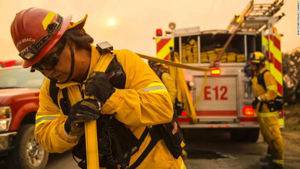 Firefighters move equipment to battle a fire in Lancaster, California, on June 2.
