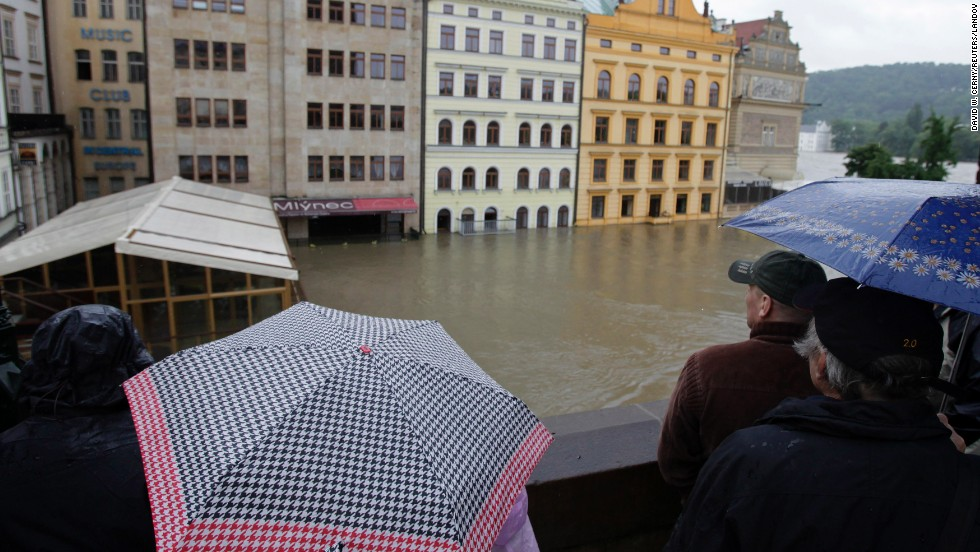 Onlookers watch the water rise around houses on the Vltava River in Prague. The Vltava was cresting Tuesday in the Czech capital, but areas downstream still faced rising waters.<br />