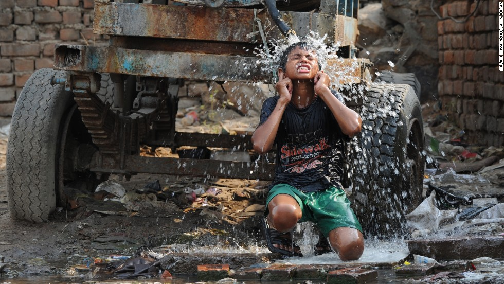 A boy cools off under a water tanker in New Delhi on Tuesday, June 4.