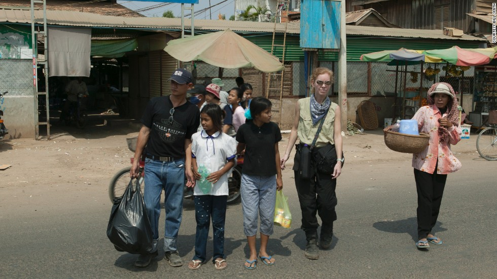 "Lauren Smith with Sreyna and Salim after a shopping trip in Cambodia. She says it didn't take much to buy clothes for the girls. ""You can get something for $2,"" she says."