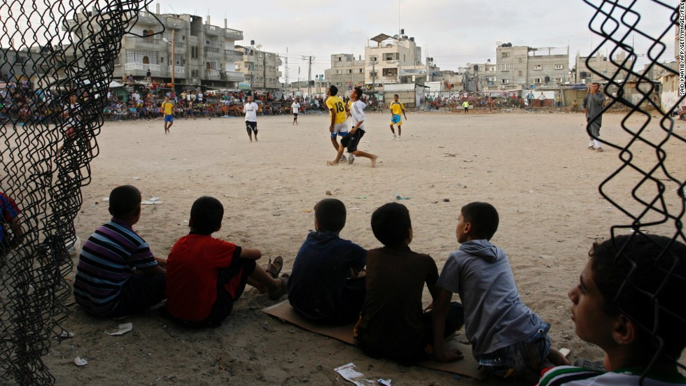 "Palestinian youths watch a local football match, just before sunset, at a refugee camp in Rafah, in the southern Gaza Strip, during the Muslim holy month of Ramadan on July 28, 2012. Sarsak grew up in Rafah, with football as his only distraction. ""It runs through the family blood,"" he says."